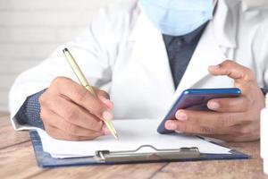 Doctor writing prescription on desk photo