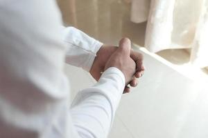Close up of young man hands in prayer photo