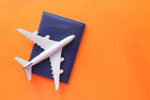 Travel vacation concept with plane and passport on orange background photo