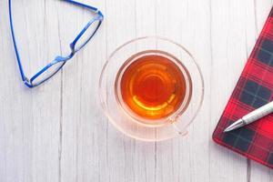 Vista de ángulo alto de té, bloc de notas y anteojos en la mesa foto