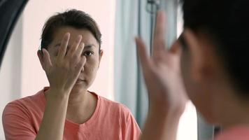 Middle-Aged Asian Woman Applying Cream to Her Face Looking at The Mirror video