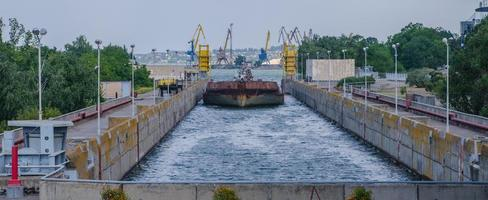 A cargo barge in the lock of a water dam