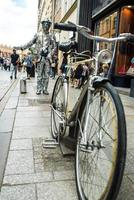 Krakow, Poland 2017- A man in a mirror suit with a suitcase and a bicycle