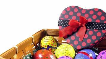 Ovos de Páscoa pascais e uma caixa de presente em formato de coração em uma cesta de madeira
