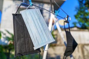 Recycled surgical face masks drying in the sun after cleaning photo