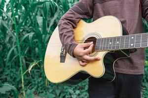 Boy playing a guitar close-up