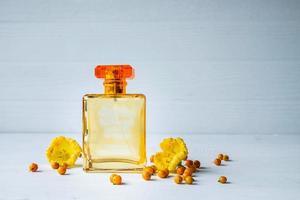 frasco de perfume con flores amarillas foto