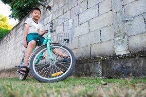 Boy sitting on a bike photo