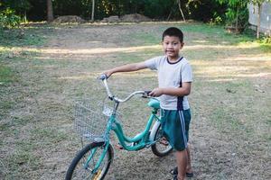 Boy walking with a bike photo