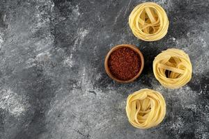 Dry tagliatelle nests and ground red pepper on a marble background