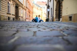 A guy and a girl on an old cobblestone street in Europe