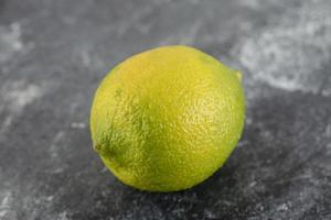 A green ripe lemon on a marble background photo