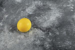 A yellow ripe lemon on a marble background photo
