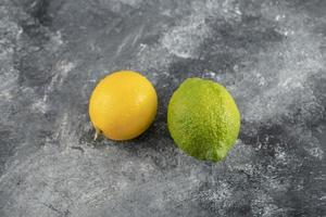 Limones amarillos y verdes sobre un fondo de mármol foto