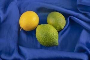 Yellow and green lemons on a blue tablecloth photo