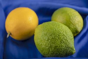 Yellow and green lemons on a tablecloth photo