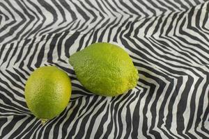limones verdes sobre un mantel foto