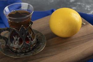 un té de cristal con un limón sobre una tabla de cortar de madera foto