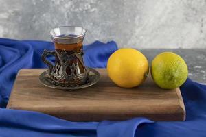un vaso de té con limones sobre una tabla de cortar de madera foto