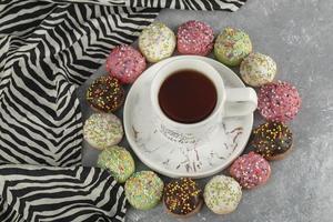 donas dulces de colores con una taza de té foto