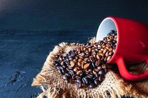 Coffee beans spilling out of a cup photo