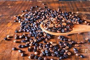 Granos de café tostados en una cuchara de madera foto