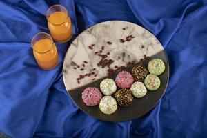 Pequeñas donas dulces de colores con botellas de jugo de naranja foto