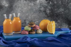 donas dulces de colores con frascos de vidrio de jugo y fruta en rodajas foto