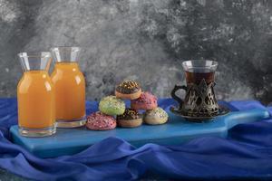 donas dulces de colores con frascos de vidrio de jugo y una taza de té foto