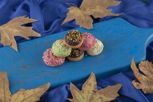 Pequeñas donas dulces de colores sobre una tabla de madera azul foto