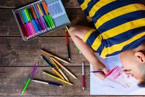 niño coloreando en el suelo foto