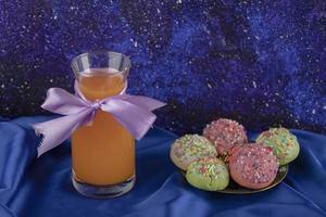 colorido juego de dulces rosquillas pequeñas con un tarro de jugo de vidrio foto