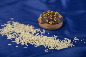 una pequeña rosquilla de chocolate con chispitas sobre un mantel azul foto