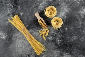 Nidos de tallarines, espaguetis y fusilli sobre un fondo de mármol foto