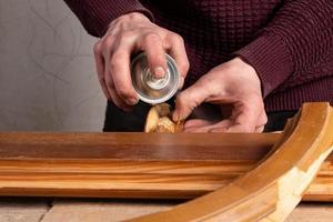 Rociar barniz sobre una puerta de madera foto