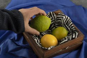 Man's hand taking a lime from a wooden basket photo