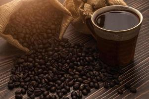 A coffee mug and coffee beans on a wooden table, love coffee concept photo