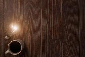 Taza de café y una bombilla que emite energía sobre una mesa de madera