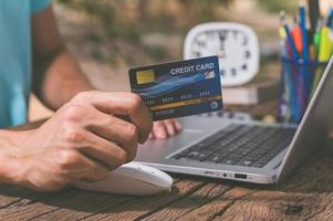 A person holding a credit card to shop online through a notebook computer photo