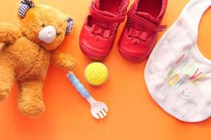 Toys for newborn on orange background photo