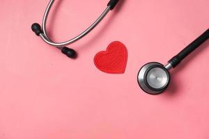 Símbolo en forma de corazón y un estetoscopio sobre fondo rosa
