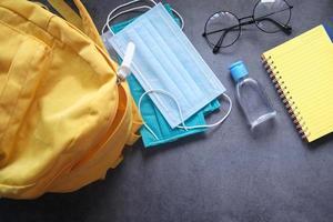 mochila escolar para estudiantes llena de desinfectante y una mascarilla