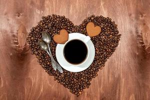 White coffee mug, heart shaped gingerbread and two spoons on a heart photo