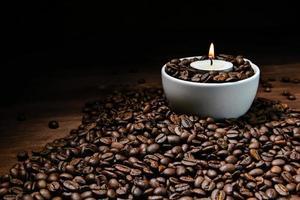 Taza de café con leche llena de granos de café y velas encendidas en la parte superior de la pila de granos de café foto