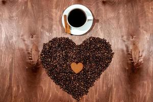 Taza de café con leche, pan de jengibre y corazón de grano de café sobre una placa de textura de madera