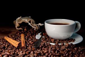 Taza de café con leche, canela en rama y granos de café en el fondo de madera oscura.