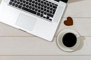 espacio de trabajo con computadora portátil, taza de café y corazón de pan de jengibre