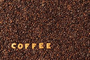 The word COFFEE made from biscuit letters on a dark coffee bean background photo