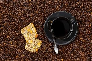 Top view of black coffee mug and cookies on the coffee beans background photo