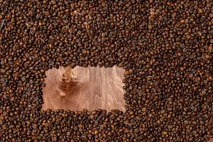 Background texture of dark wooden board and frame of coffee beans photo